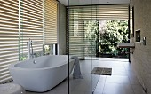 Designer bathroom with free-standing bathtub in front of glass wall with half-closed louver blinds