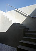 Minimalist, winding, exterior concrete staircase with stainless steel handrail on wall below a blue sky