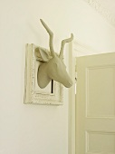 White gazelle's head in white picture frame as wall decoration