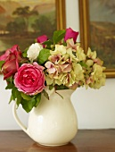 Summery bouquet of roses and hydrangeas in jug in front of oil painting