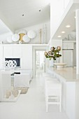 White, modern interior with bar stools at kitchen counter opposite lounge area with collection of swords and shields on top of fitted cupboards