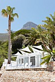 Terrace with white awnings adjoining house with stone walls in South African landscape