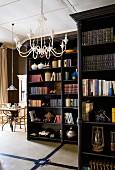 Dunkel lackierte Bücherregale im Raum stehend und weisser Metall Lüster an Decke in offenem Wohnbereich