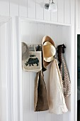 Beach house coat rack in niche below sconce lamp