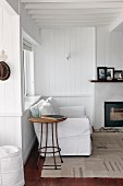 White couch and small side table in peaceful corner of room next to wood-burning stove; photographs in black frames on mantelpiece