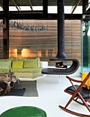 Floating wood-burning stove in modern living room with spring green couch and rustic, root-wood coffee table in front of rammed earth wall