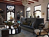 Eclectic collection of objets d'art in grand living room with art nouveau windows and soft couch with high backrest