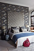 Magnificent bed with quilted, tall headboard against slate grey, floral wallpaper and matching scatter cushions on bed