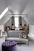 Metal four-poster bed, silver grey couch at foot of bed and purple ottoman in attic room with sloping ceiling