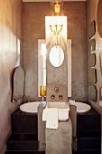 Free-standing concrete column with sink, tap fittings and candle sconce above mirror in front of black platform with sunken bathtub