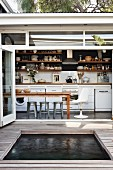 Sunken pool in wooden deck in front of open, folding terrace doors with view of dining area and kitchen counter