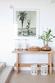 Gerahmtes schwarz-weiss Foto über einfachem Wandtisch mit großen Windlichtern und einer Topfpflanze