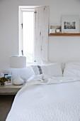 Offener Fensterladen über Bett mit weißem Bettüberwurf und darüberhängendem Holzboard mit an der Wand angelehnten Fotos