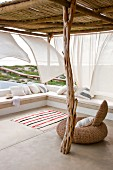Rustic, driftwood roof support on airy terrace with fluttering curtains and sea view