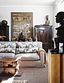 Living room with antique, Chinese wooden furniture and objets d'art from around the world; sofa with soft upholstery in foreground with wooden, sculptural coffee table