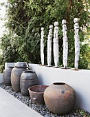 Row of statues of women on low wall above collection of large vases