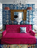 Spacious deep pink couch in luxurious room; wallpaper with large pattern, crystal chandelier and silk rug with large floral pattern