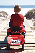 Little boy on toy tractor driving along a wooden boardwalk
