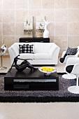 Living room with white leather couch, black and white objet d'art and black coffee table
