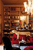 Grand library with integrated wall mirror, leopard skin on back of sofa and crystal chandelier