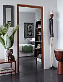 Kunstobjekte und eine Djembe vor dem Durchgang zum Schlafzimmer; Kontrast von Holzrahmen und poliertem Sichtestrich