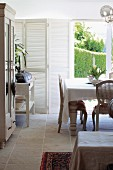 Rustic Rococo style - dining area in front of terrace door with view of garden and white folding window shutters