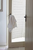 Anteroom with open, white doors; towel hanging on nostalgic door handle
