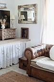 Brown leather sofa in front of window next to wooden surface with lace curtain in corner of room