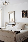 Pale, antique sleigh bed next to simple bedside table and framed mirror on wall