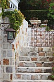 View up stone steps of wrought iron gate leading to terrace seating area and hedge in manorial setting