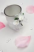 Tealight holder decorated with ribbon and white flowers amongst scattered rose petals