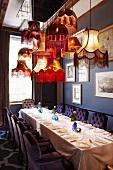 Gedeckte Esstafel unter nostalgischem Lampenhimmel; die Stühle mit gesteppter Rückenlehne harmonieren mit der blauen Wandfarbe