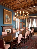 Opulent, long wooden table in front of marble fireplace in lavish dining room with elaborately carved coffered ceiling