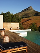 Infinity pool with integrated whirlpool; expansive wooden deck with comfortable sun loungers in foreground