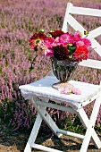 Summer bouquet of dahlias and heather on garden chair