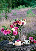 A garden table laid with Bundt cake, teacup, summer flowers and a hurricane lamp