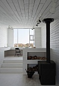 Interior with white wooden walls and wood-burning stove (Bridge Studio, Fogo Island, Canada)