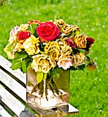 Wilted bouquet of roses on garden table