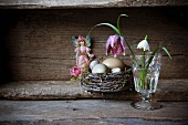 Still-life of various eggs in nest, snake's head fritillary and snowdrop in drinking glass and sticker of fairy figure in old wooden crate