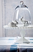Two white china rabbits on cake stand with glass cover
