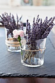 Sprays of lavender flowers in glass holders as table decorations