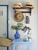 Several straw hats on coat rack above Chinese porcelain vase on vintage table