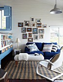 Cheerful blue and white living room below sloping ceiling; collection of photos in vintage picture frames above couch