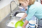 Mädchen wäscht Geschirr in der Küche ab