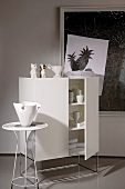 White crockery in designer cabinet with ornaments on top and vase on small side table in front of contemporary artwork