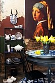 Dutch china crockery and ornaments in small cabinet, painting on wall and vase of tulips on table