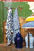 Blue and white patterned tea towels on wall hooks, storage jars and scatter cushions on bench