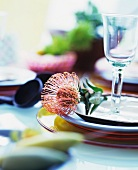 Place setting with tropical flower and wine glass