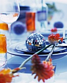 Disco ball, sprigs of flowers & decorative fish on place setting