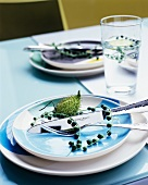 Stalk of berries and flower bud decorating place setting and in glass of water on table